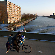 "Nederland Utrecht 31 januari 2009 20090131 Foto: David Rozing ..Serie vogelaarwijk Kanaleneiland .Reportage documentary on deprived area / projects "" Kanaleneiland "" This area is on a list with projects which need help of the government because of degradation in the area etc.Fietser steekt brug over, zicht op kanaleneiland zuid, watergang, water, kanaal en flat .Biking, cyclist on bridge with view on canal water flat, Kanaleneiland zuid. project, suburb, suburbian, problem. Neighboorhood, neighboorhoods, district, city, problems, daily lifeFoto: David Rozing"