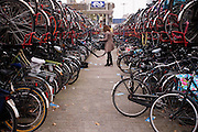 Een vrouw stalt haar fiets in de overvolle fietsenstallingen bij het station van Utrecht.<br /> <br /> Bike parking at Utrecht Central Station