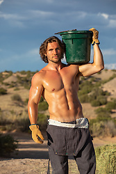 hot shirtless muscular tan man with a water bucket outdoors