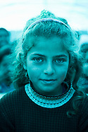 Rahaf el Saleh, age 10, at school in the displaced persons camp in Atmeh, Syria. Blue hue cast by blue tarp roof.