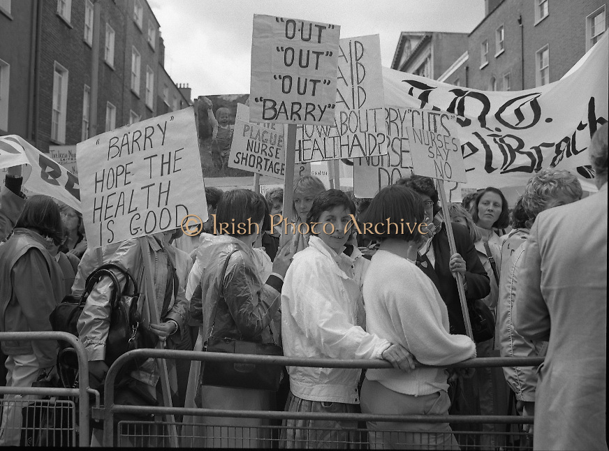 "Irish Nurses Organisation Protest..28.05.1986..05.28.1986..28th May 1986..In protest against proposed health cuts the Irish Nurses Organisation organised a protest march to Dail Eireann. Nurses from all over Ireland were represented at the march...Image shows nurses gathering at the barrier in front of Leinster House. The ""Barry"" referred to on the placards is the Minister for Health Mr Barry Desmond TD."