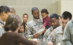 Spc Colin Lanhan holds his son Coltin while in line at a Thanksgiving dinner for soldiers of JBLM held in Chris Knutzen hall of the Anderson University center on Wednesday, Nov. 26, 2014. (Photo/John Froschauer)