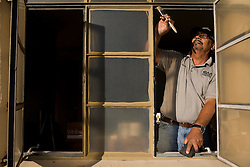 Jessi Avalos weatherizes a window.  He works for the Community Action Agency(CAA). The CAA received stimulus funding and, among other things, works on weatherizing the homes of poor families and individuals in New Mexico.