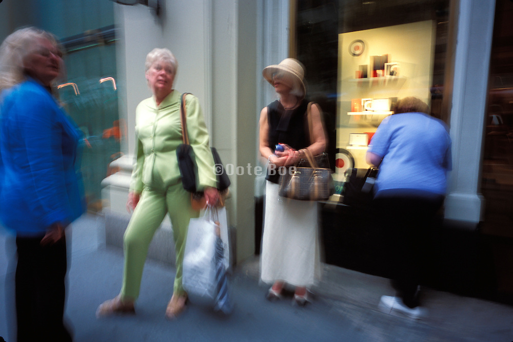 People window shopping and talking on Fifth Avenue