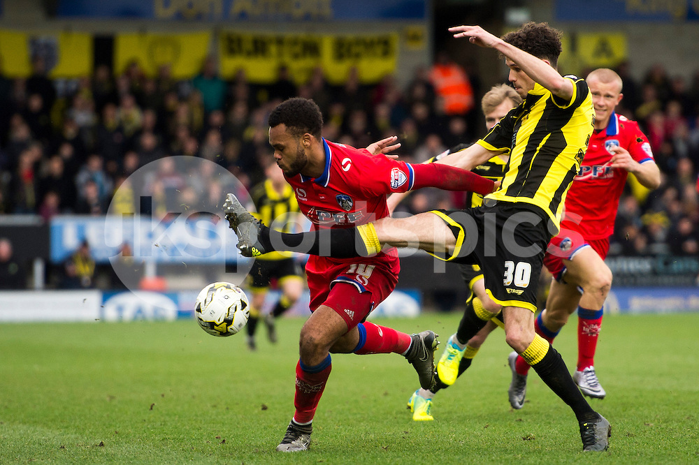 Tom Flanagan of Burton Albion and Aaron Amadi-Holloway of Oldham Athletic AFC compete for the ball during the Sky Bet League 1 match between Burton Albion and Oldham Athletic at the Pirelli Stadium, Burton upon Trent, England on 26 March 2016. Photo by Brandon Griffiths.
