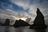 seastacks at Bandon Oregon beach silouetted against sunset through cloud