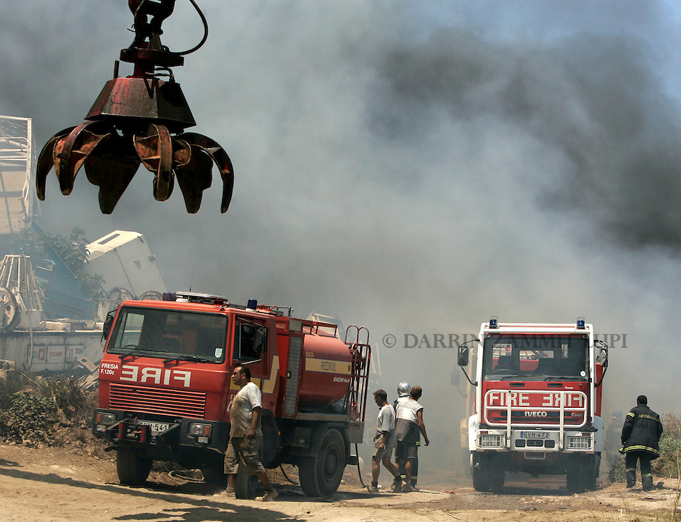 Civil Protection units tackle a large fire in a quarry used as a scrap yard for cars in Marsa, outside Valletta, July 3, 2006.  Palls of rising toxic black smoke could be seen from all over the island...MALTA OUT..REUTERS/Darrin Zammit Lupi (MALTA)
