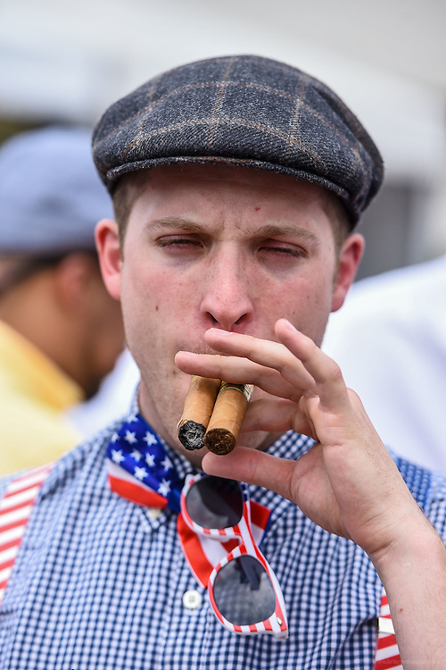 Jarrod Swick of Eerie, Pa., works two cigars at the 142nd running of the Kentucky Derby. May 7, 2016