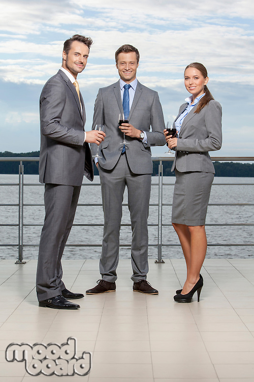 Full length portrait of young businesspeople holding wineglasses on terrace