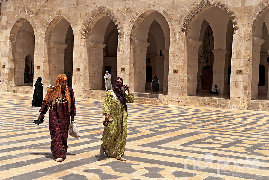 Two women cover their faces while crossing the courtyard of Aleppo's main mosque