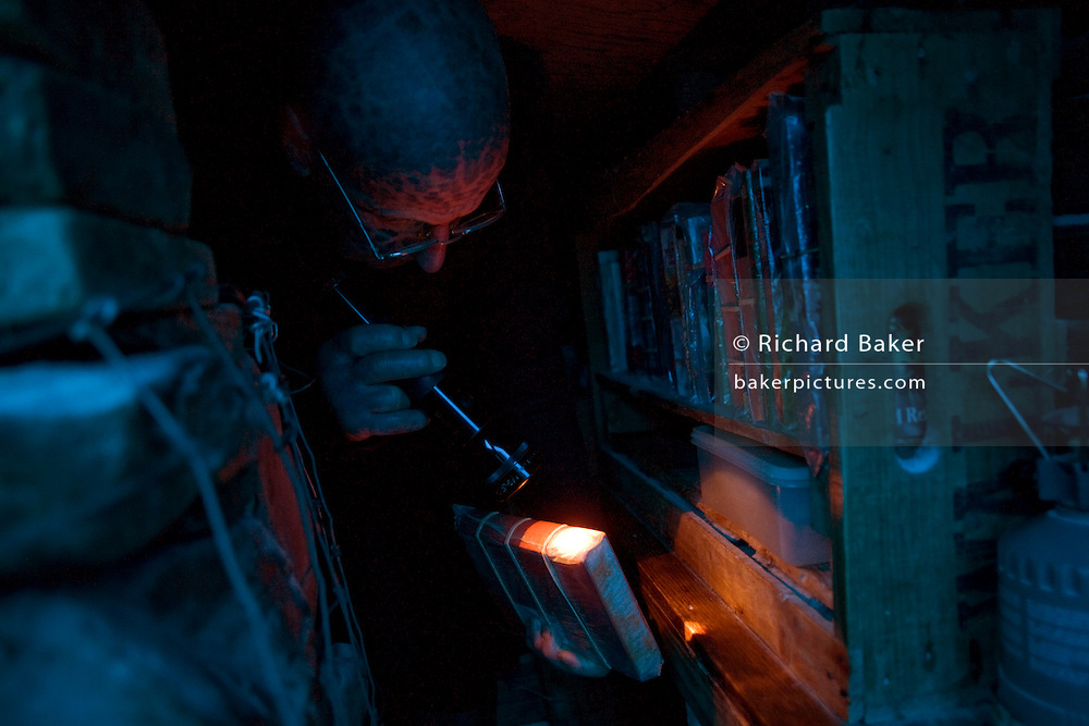 Tattoed hermit Tom Leppard (the Leopard Man) looks through wrapped books in his makeshift underground library, Isle of Skye