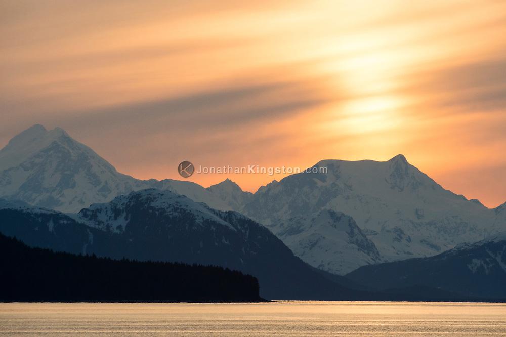 Sunset over snow capped peaks of Glacier Bay National Park.