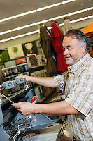 Mature man looking at price tag of machinery in hardware store