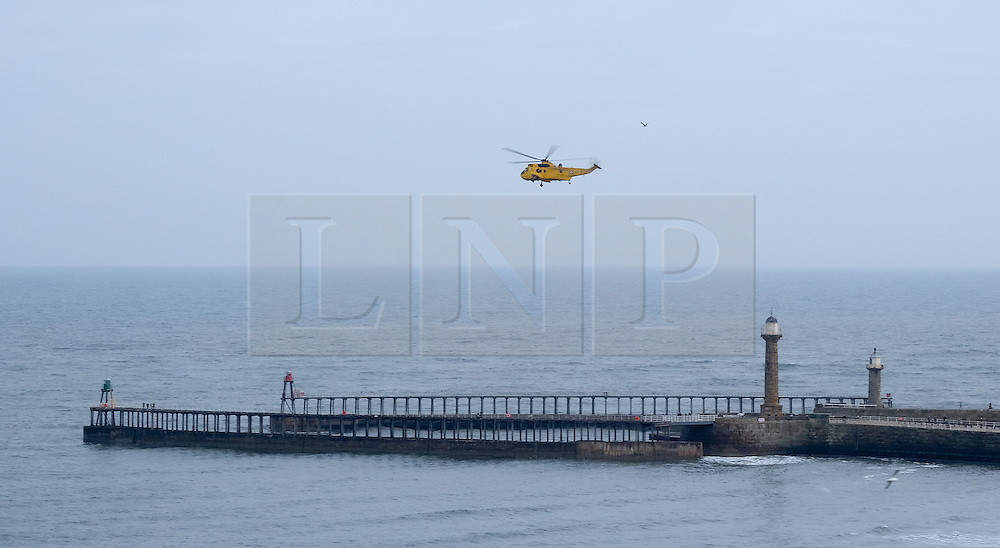 © Licensed to London News Pictures. <br /> 15/03/2015. <br /> <br /> Whitby, United Kingdom<br /> <br /> A Royal Air Force Sea king Search and Rescue helicopter, call sign Rescue 128 does a fly-by over the East and West piers in Whitby in North Yorkshire. This was the final flight for this helicopter and as a way to say goodbye to members of the public it landed in Whitby.<br /> <br /> Photo credit : Ian Forsyth/LNP