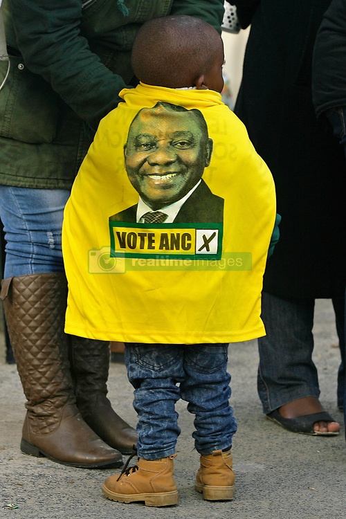 Wednesday 8th May 2019.<br /> Monwabisi Park, Harare,<br /> Khayelitsha, Cape Town, <br /> Western Cape, <br /> South Africa.<br /> <br /> SOUTH AFRICAN GENERAL ELECTIONS 2019!<br /> <br /> SOUTH AFRICAN PROVINCIAL AND NATIONAL ELECTIONS 2019! <br /> <br /> A young boy wears an ANC political party t-shirt as a cape as he and family members enjoy the somewhat festive activities on Election Day outside the voting station at Monwabisi Park, Harare in Khayelitsha near Cape Town, Western Cape, South Africa.<br /> <br /> Registered South African Voters head to the various IEC (Independent Electoral Commission) Voting Stations where they are registered to vote as they cast their votes and take part in voting and other activities on Voting Day 8th May 2019 during the South African General Elections 2019. Voters from across the nation stood in queue's along with many others to vote in the Provincial and National Elections being held in South Africa on Wednesday 8th May 2019.   <br />  <br /> Copyright © Mark Wessels. All Rights Reserved. No Usage Without Permission.<br /> <br /> PICTURE: MARK WESSELS. 08/05/2019.<br /> +27 (0)61 547 2729.<br /> mark@sevenbang.com<br /> studioseven@mweb.co.za<br /> www.markwesselsphoto.com