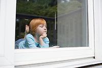 Young girl (5-6) indoors looking through window