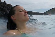 Young woman enjoying bathing in hot spring. Blue Lagoon. Iceland.