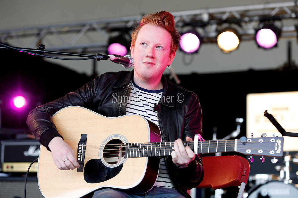READING, ENGLAND - AUGUST 26:  Alex Trimble of Two Door Cinema Club performs live on the BBC Introducing Stage on Day Three during the Reading Festival 2012 at Richfield Avenue on August 26, 2012 in Reading, England. Two Door Cinema Club, played a secret acoustic set ahead of their headline set on Radio 1 NME stage this evening. (Photo by Simone Joyner/Getty Images)