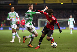Yeovil Town's Tom James (left) and Manchester United's Angel Gomes (right) battle for the ball during the Emirates FA Cup, fourth round match at Huish Park, Yeovil.