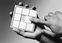 Hands holding slide puzzle (b&w) (close-up)