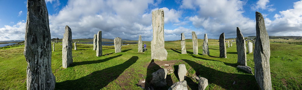 "Erected 4600 years ago, the Callanish Standing Stones are one of the most spectacular megalithic monuments in Scotland. The main site known as ""Callanish I"" forms a cross with a central stone circle erected circa 2900-2600 BC. More lines of stones were added by 2000 BC (the close of the Neolithic era), and it become a focus for rituals during the Bronze Age. From 1500-1000 BC, farmers emptied the burials and ploughed the area. After from 800 BC, peat accumulated 1.5 meters deep and buried the stones until removed in 1857. Visit this spectacular ancient site near the village of Callanish (Gaelic: Calanais), on the Isle of Lewis, Outer Hebrides (Western Isles), Scotland, United Kingdom, Europe. This image was stitched from several overlapping photos."