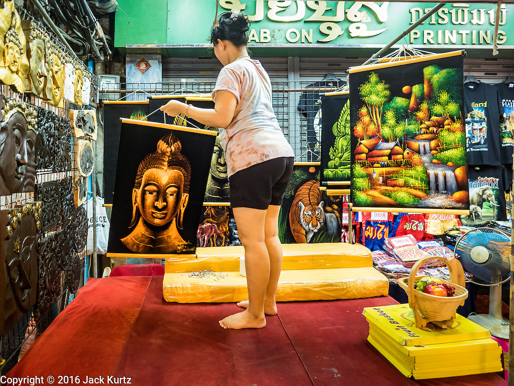 26 MAY 2016 - BANGKOK, THAILAND: A woman who sells Thai art in the Silom Road night market sets out her merchandise. The night market on Silom Road, close to Bangkok's famous Patpong tourist area, is being closed by the Bangkok municipal government. Vendors have been told they have to leave the sidewalk on Silom Road by the end of May, 2016. The market is the latest street market being shut down by city officials as a part of the government's plan to clean up Bangkok. The Silom Road night market sells mostly tourist oriented clothes, inexpensive Thai art, and bootleg movies on DVD.       PHOTO BY JACK KURTZ