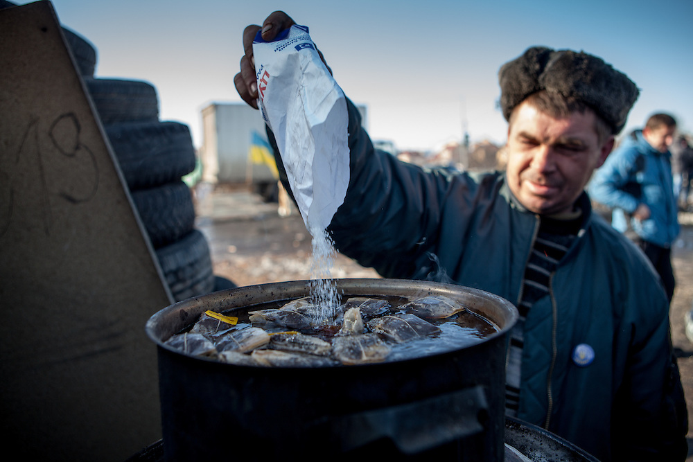"""Activist """"Bosch"""" putting sugar into a huge pot of tea at the barricades blocking a building supplies store named """"Epicenter"""" in the city of Lviv, Ukraine."""