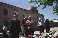 Men arriving for prayers at the Haji Yakoub mosque stop to read and buy books of Islamic texts and teachings, in Dushanbe, Tajikistan.