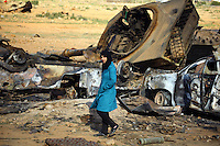 A young woman walks among the wreckage of pro-Ghaddafi tanks and armoured personnel carriers at the site of a staging area outside Benghazi devastated by coalition forces enforcing the no-fly zone over eastern Libya. 22 March