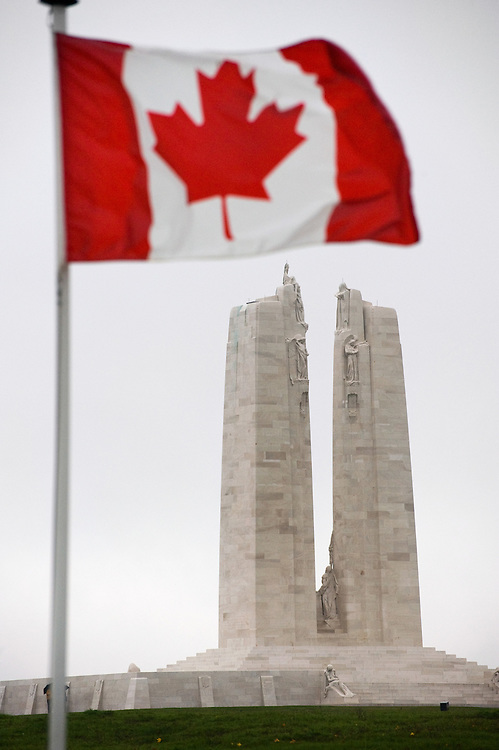 The Canadian flag flying at the Canadian National Vimy Memorial dedicated to the memory of Canadian Expeditionary Force members killed in World War one. The monument is situated at a 100 hectare preserved battlefield with wartime tunnels, trenches, craters and unexploded munitions. The memorial designed by Walter Seymour Allward opened in 1936.