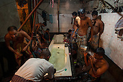 Men bathe after work in a public bath near the Mach Bazaar. Part of a story on life in Bangladesh's capital after being voted the worst city in the world to live.
