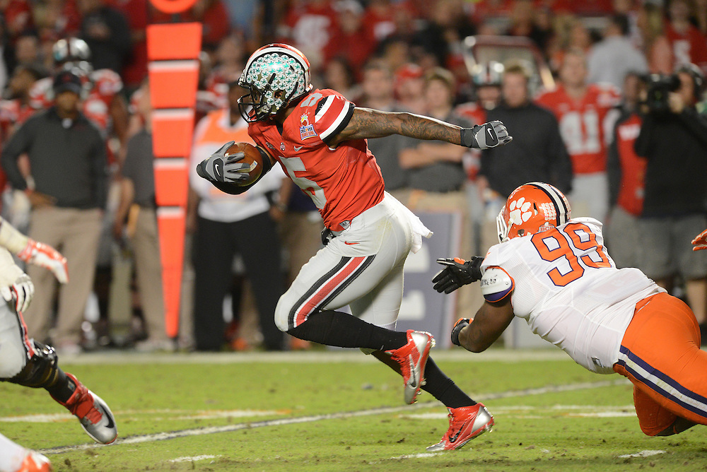 January 3, 2014: DeShawn Williams #99 of Clemson attempts to tackle Braxton Miller #5 of Ohio State during the NCAA football game between the Clemson Tigers and the Ohio State Buckeyes at the 2014 Orange Bowl in Miami Gardens, Florida. The Buckeyes led the Tigers 22-20 at the half.