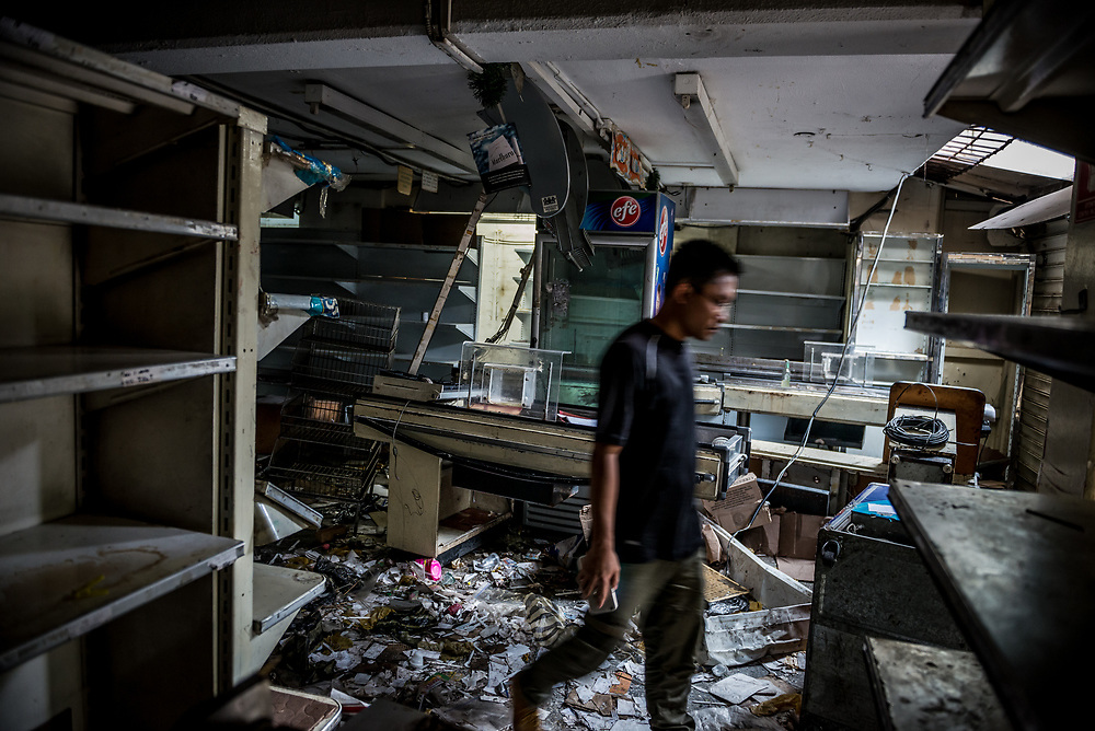 "CARACAS, VENEZUELA - APRIL 21, 2017:  Jian Feng Wu inspects the damage to Vicruz supermarket, that was one of over a dozen stores looted late last night in El Valle, a working class neighborhood in Caracas. ""They took everything,"" he said. The streets of Caracas erupted into a night of riots, looting and clashes with National Guardsmen as anger from two days of pro-democracy protests spilled into unrest in working class neighborhoods and slums. Shots rang out throughout the night in El Valle, a neighborhood of mixed loyalties, as armored vehicles struggled to contain crowds of looters. At one point during the night, clashes became so heavy that a nearby children's hospital was evacuated after the ward filled with tear gas. The government said they were responding to an attack on the hospital by opposition protestors.  PHOTO: Meridith Kohut"