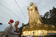 Songnisan National Park. Beopjusa Temple. Monk and the 33m high, 160 ton golden Buddha statue.