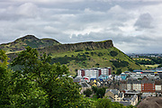 Arthur's Seat (822 feet elevation) rises behind Salisbury Crags in Holyrood Park above Edinburgh, in Scotland, United Kingdom, Europe. Holyrood Park holds a special place in the history of science: Edinburgh geologist James Hutton (1726-97), the father of modern geology, recognised that the Crags' rock had been injected in a molten state into older sedimentary rocks, disproving previous theories. He suggested that the Earth was very old, and continually changing. This startlingly new idea changed the way people thought about the earth, influencing other scientists such as Charles Darwin. The Crags' hard dolerite was quarried for street cobblestones from the mid-1600s until 1831, when the House of Lords decreed that no more stone should be removed, in order to protect the iconic landscape. The Crags are the glaciated remains of a Carboniferous dolerite sill, injected between sedimentary rocks which formed in a shallow sea some 340 million years ago. Glaciers sweeping outwards from the center of Scotland within the past 2 million years scraped this ancient geology into its present form.