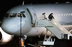 © Licensed to London News Pictures. 02/02/2020. Brize Norton, UK. Two passengers, one carrying a baby in a carry cot, who were evacuated from Wuhan in China disembark at RAF Brize Norton in Oxfordshire. On Friday 83 Britons were flown from the centre of the coronavirus outbreak to RAF Brize Norton and then transported to quarantine for 14 days at Arrowe Park Hospital on the Wirral. Photo credit: Peter Macdiarmid/LNP