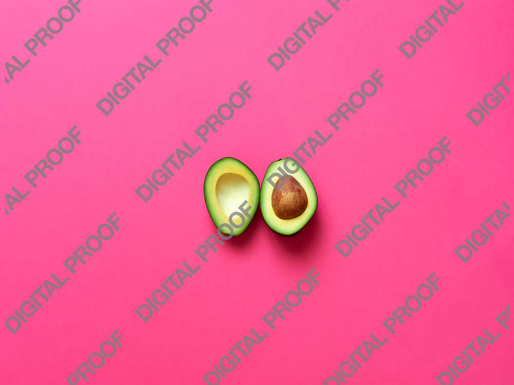 Avocado sliced with seed isolated in fuscia background viewed from above - flatlay look