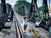 "09 JANUARY 2019 - KANCHANABURI, THAILAND: A local woman walks across the ""Bridge On the River Kwai"" in Kanchanaburi. Hundreds of thousands of Asian slave laborers and Allied prisoners of war died in World War II constructing the ""Death Railway"" between Bangkok and Rangoon (now Yangon), Burma (now Myanmar) for the Japanese during World War II.  The bridge is now one of the most famous tourist attractions in Thailand.     PHOTO BY JACK KURTZ"
