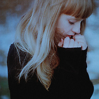 Young woman with long blonde hair wearing black sweater with hands held to face and sad expression