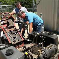 Johnson and Hopkins work to identify what parts are needed to repair a customer's mower so a price quote can be given.