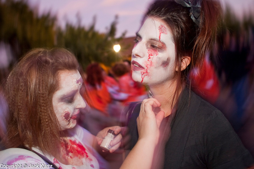 "Oct. 30, 2009 -- PHOENIX, AZ: WHITNEY KOBEY, left, helps CORY GALVAN, both Arizona State University students, put on Zombie makeup before the Zombie Walk in Phoenix Friday. About 200 people participated in the first ""Zombie Walk"" in Phoenix, AZ, Friday night. The Zombies walked through downtown Phoenix ""attacking"" willing victims and mixing with folks going to the theatre and downtown sports venues.  Photo by Jack Kurtz"