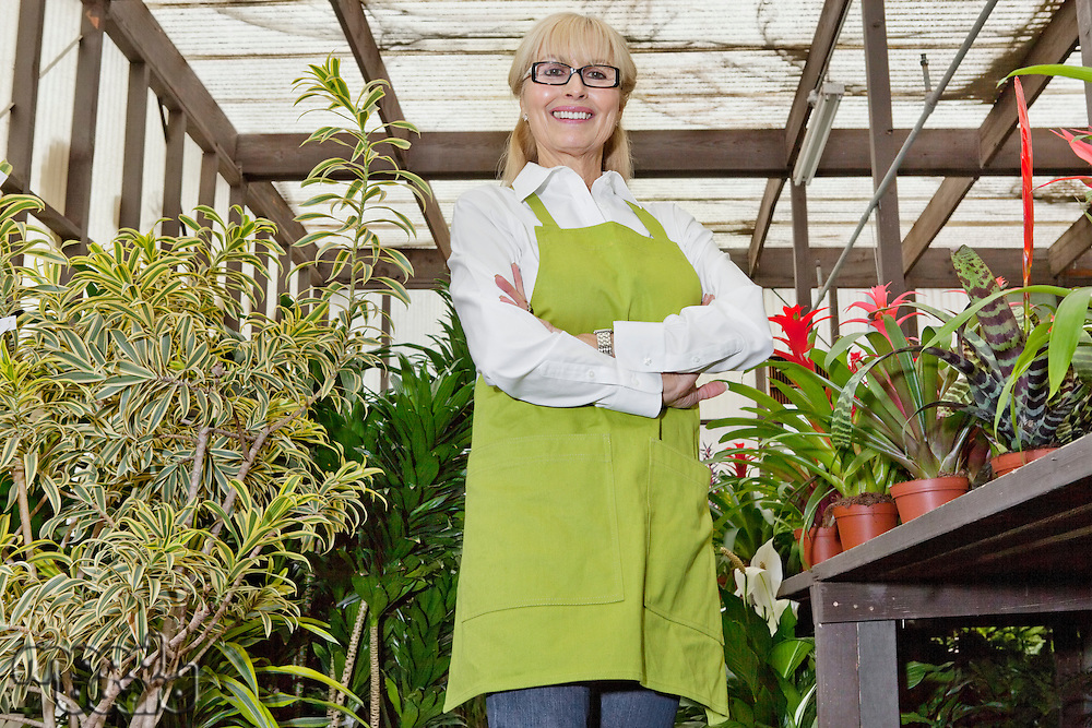 Portrait of a happy female gardener standing with arms crossed in botanical garden