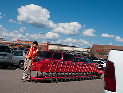 A young man catches a ride on a remote controlled robotic shopping cart pusher in a store parking lot