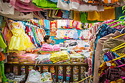 "12 APRIL 2012 - HO CHI MINH CITY, VIETNAM:   A children's clothing vendor in her shop in Binh Tay Market. Binh Tay market is the largest market in Ho Chi Minh City and is the central market of Cholon. Cholon is the Chinese-influenced section of Ho Chi Minh City (former Saigon). It is the largest ""Chinatown"" in Vietnam. Cholon consists of the western half of District 5 as well as several adjoining neighborhoods in District 6. The Vietnamese name Cholon literally means ""big"" (lon) ""market"" (cho). Incorporated in 1879 as a city 11 km from central Saigon. By the 1930s, it had expanded to the city limit of Saigon. On April 27, 1931, French colonial authorities merged the two cities to form Saigon-Cholon. In 1956, ""Cholon"" was dropped from the name and the city became known as Saigon. During the Vietnam War (called the American War by the Vietnamese), soldiers and deserters from the United States Army maintained a thriving black market in Cholon, trading in various American and especially U.S Army-issue items.       PHOTO BY JACK KURTZ"