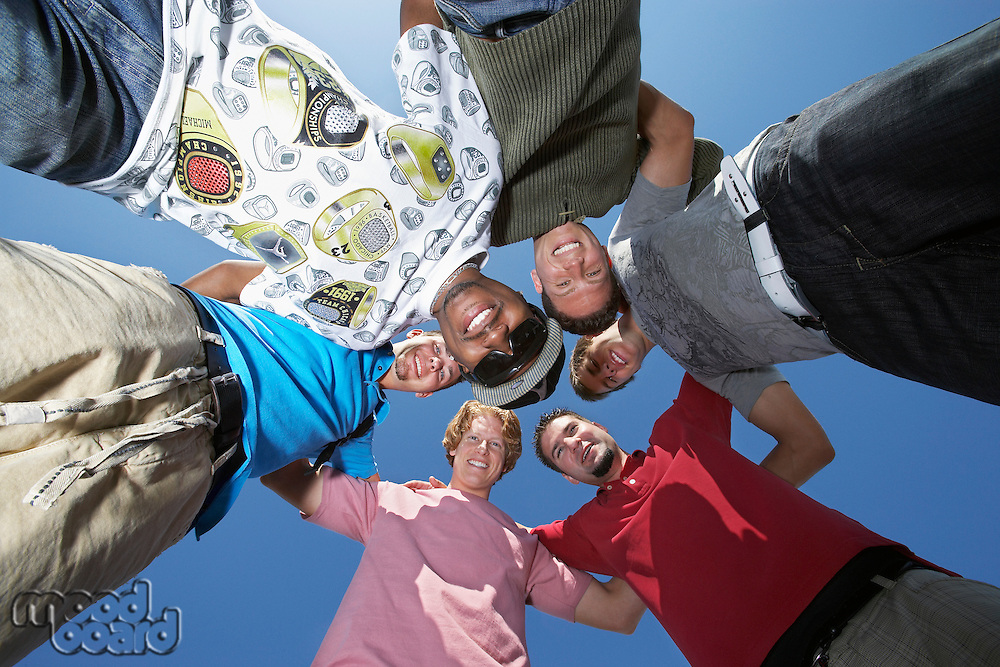 Group of young men in circle, view from below
