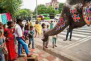 6th September 2014, New Delhi, India. While an elephant handler has breakfast at a restaurant children feed the elephant snacks and try to touch her trunk, near New Rajinder Nagar, New Delhi, India on the 6th September 2014<br /> <br /> Elephant handlers (Mahouts) eke out a living in makeshift camps on the banks of the Yamuna River in New Delhi. They survive on a small retainer paid by the elephant owners and by giving rides to passers by. The owners keep all the money from hiring the animals out for religious festivals, events and weddings, they also are involved in the illegal trade of captive elephants. The living conditions and treatment of elephants kept in cities in North India is extremely harsh, the handlers use the banned 'ankush' or bullhook to control the animals through daily beatings, the animals have no proper shelters are forced to walk on burning hot tarmac and stand for hours with their feet chained together. <br /> <br /> PHOTOGRAPH BY AND COPYRIGHT OF SIMON DE TREY-WHITE<br /> + 91 98103 99809<br /> email: simon@simondetreywhite.com photographer in delhi