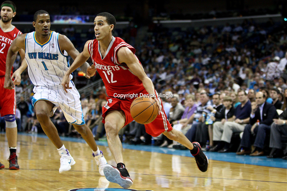 April 6, 2011; New Orleans, LA, USA; Houston Rockets shooting guard Kevin Martin (12) drives past New Orleans Hornets small forward Trevor Ariza (1) during the third quarter at the New Orleans Arena. The Hornets defeated the Rockets 101-93 and clinched a playoff spot with the victory.   Mandatory Credit: Derick E. Hingle-US PRESSWIRE