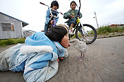 Girl playing with a baby seagull in Newtok, Alaska. 2008