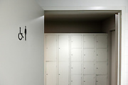 toilet door with male and handicap sign at end of hall with closet hand luggage storage