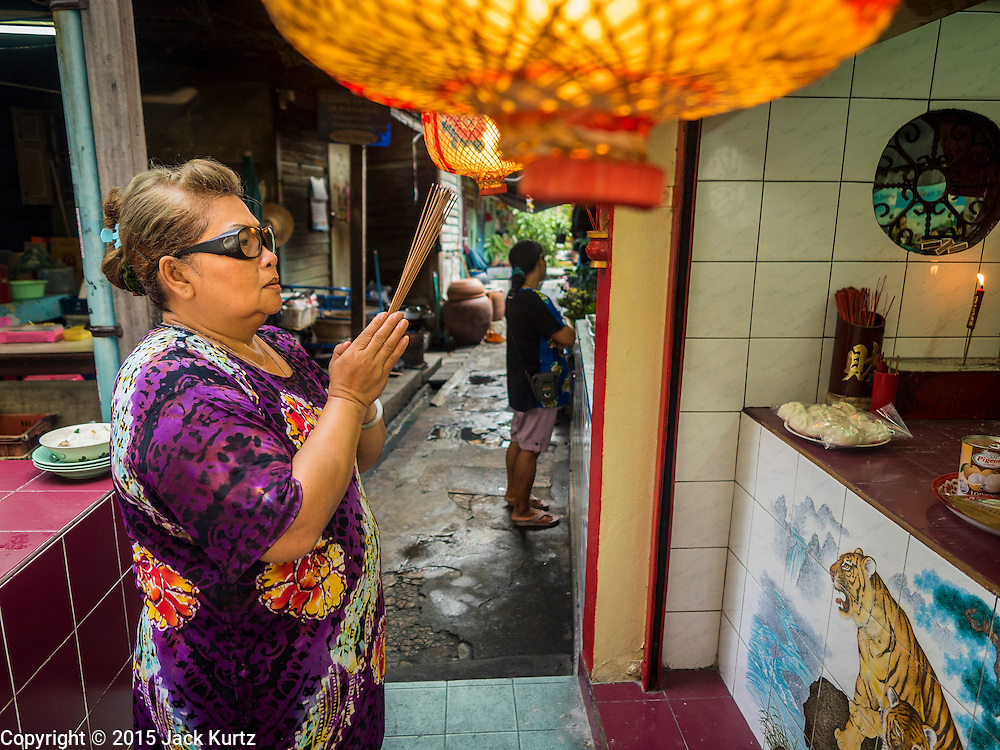 28 AUGUST 2015 - BANGKOK, THAILAND:  A woman prays at a small shrine in Bangkok's Chinatown on Hungry Ghost Day. Mahayana  Buddhists believe that the gates of hell are opened on the full moon of the seventh lunar month of the Chinese calendar, and the spirits of hungry ghosts allowed to roam the earth. These ghosts need food and merit to find their way back to their own. People help by offering food, paper money, candles and flowers, making merit of their own in the process. Hungry Ghost Day is observed in communities with a large ethnic Chinese population, like Bangkok's Chinatown.     PHOTO BY JACK KURTZ